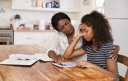 Modern hjälper den stressade tonårs- dottern med läxa royaltyfri foto