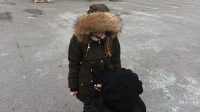 Modern hjälper hennes dotter ordnar en omslagshuv arkivfilmer