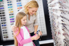 Modern hjälper hennes flicka att välja den bra ramen för glasögon Arkivfoton
