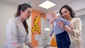Modern hjälper hennes litet barnställning framme av en doktor arkivfilmer