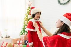 Modern hjälper hennes unge att klä upp jultomten Fotografering för Bildbyråer