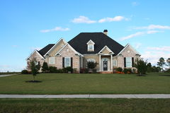 Modern Home. Built with brick and stone on landscaped yard Stock Photos