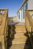 Modern Home & Deck. Front deck made of natural wood attached to a modern, newly built modular home. Room for text in the blue sky Royalty Free Stock Photos