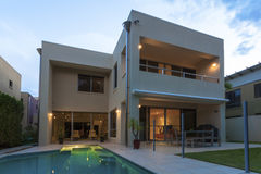 Modern home exterior at dusk. Modern home exterior with pool at dusk Stock Photography