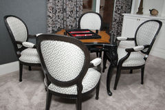 Modern Home Game  Room Area. Luxury home game room area with wood table, carpeted floors and upholstered chairs Stock Photo