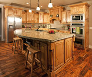Modern Home Kitchen Center Island. Modern home with lovely custom kitchen cabinets, countertops and center island Stock Images