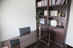 Modern home office with bookshelves and sculptures. Royalty Free Stock Photography