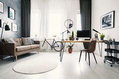 Modern home office interior with a big window, sofa, bike and de. Sk with a computer. Real photo stock image