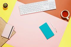 Modern home office workspace. Flat lay composition of keyboard, cactus, diary, notebook with pen and cup of tea on. Colorful desk. Pink, yellow, aquamarine and Stock Image
