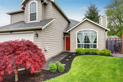 Modern home with red door and light grey exterior. Royalty Free Stock Photo
