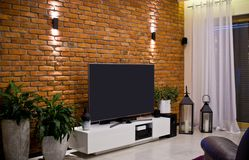 Modern home room design with red brick wall and flat led television royalty free stock photos