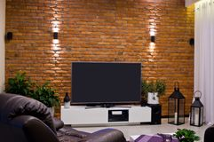 Modern home room design with red brick wall and flat led television. Home architecture: modern room of a house, living room design with red brick wall and LED stock photography