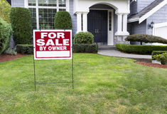Modern Home for Sale with sign in front yard. Closeup view of Modern Suburban Home for Sale Real Estate Sign in front of modern home Royalty Free Stock Photography