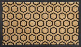 Modern Honeycomb design peach color doormat with black border. Isolated on a White Background stock photography