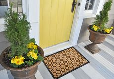 Modern Honeycomb design peach color doormat with black border Placed outside door. With green leaves stock photography