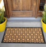 Modern Honeycomb design peach color doormat with black border Placed outside door. With green leaves royalty free stock images