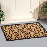 Modern Honeycomb design peach color doormat with black border Placed outside door. With green leaves stock images