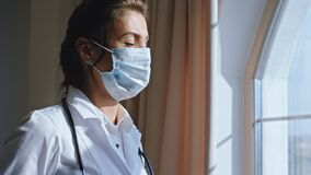 Modern hospital in the stuff room portrait of a tired and sad woman doctor wearing a protective mask she looking through