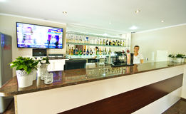 Modern hotel bar in Poland. Bright modern hotel bar in Poland with pot plants with variegated leaves on the bar, a widescreen television on the wall behind and a royalty free stock images