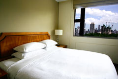 Modern hotel bedroom overlooking the cityscape. Royalty Free Stock Photo