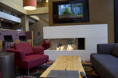 Modern hotel lobby fireplace. Comfortable furniture and modern fireplace in a 4 star hotel Stock Photography