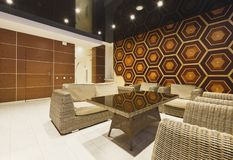 Modern hotel lobby with wicker furniture. Modern lobby with wicker furniture, abstract wooden wall with honeycomb pattern. Rest zone in modern hotel, copy space royalty free stock photos