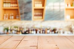 Modern hotel lounge and bar with the shelfe of alcoholic drinks. Empty wooden bar counter with defocused background and bottles of Modern hotel lounge and bar Royalty Free Stock Image