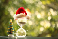 Modern Hourglass and Christmas tree. Christmas countdown. Modern Hourglass and Christmas tree -- sand trickling through the bulbs of a crystal sand glass. space Royalty Free Stock Image