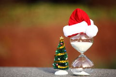 Modern Hourglass and Christmas tree. Christmas countdown. Modern Hourglass and Christmas tree -- sand trickling through the bulbs of a crystal sand glass. space Royalty Free Stock Photo