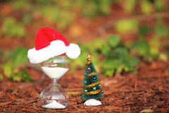 Modern Hourglass and Christmas tree. Christmas countdown. Modern Hourglass and Christmas tree -- sand trickling through the bulbs of a crystal sand glass. space Royalty Free Stock Photography