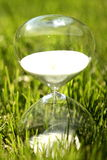 Modern hourglass on green background. Stock Image