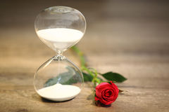 Modern hourglass and red rose with copy space. Valentines day countdown Stock Photos