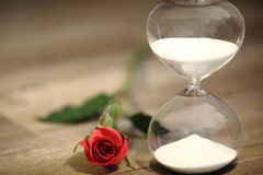Modern hourglass and red rose with copy space. Valentines day countdown Royalty Free Stock Image