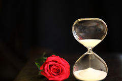 Modern hourglass and red rose with copy space. Valentines day countdown Stock Images