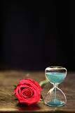 Modern hourglass and red rose with copy space. Valentines day countdown Royalty Free Stock Photo