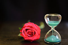 Modern hourglass and red rose with copy space. Valentines day countdown Royalty Free Stock Photography