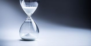 Modern hourglass in running time in studio lights royalty free stock photo