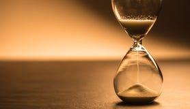 Modern hourglass in running time in studio lights stock image