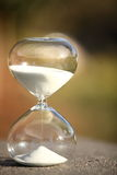 Modern Hourglass. symbol of time. countdown. Modern Hourglass -- sand trickling through the bulbs of a crystal sand glass. symbol of time. countdown. Time Royalty Free Stock Image