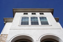 Modern House. A modern stucco house reaching into the blue sky Royalty Free Stock Photos