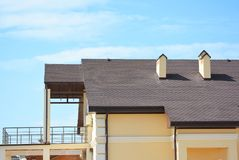 Modern house with balcony terrace, roof gutter system, asphalt shingles roofing. Stock Photography