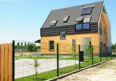 Modern House Building with energy saving and energy efficiency. Eco-house or eco-home. Roofing Construction with attic window skylights, solar panels and solar Stock Photography