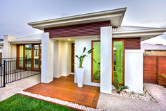 Modern house entrance with a wooden and concrete yard with a law Stock Photos