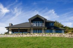 Modern House Exterior 1. A luxurious modern home positioned on a hill top with vibrant blue skies Stock Photography