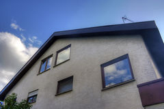 Modern house exterior. Low angle exterior view of modern house with cloudscape reflecting on windows Stock Photo