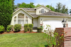 Modern house exterior with curb appeal. Modern house exterior with garage. Front yard landscape with trimmed bushes and green lawn Stock Images