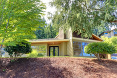Modern house exterior with curb appeal. View from driveway. Modern house exterior with curb appeal. View of glass walls and entrance porch Royalty Free Stock Images