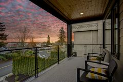 Modern house exterior with a deck at sunset. Modern house exterior with private deck overlooking downtown Kirkland at sunset royalty free stock images