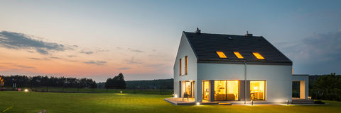 Modern house with garden at night. Panoramic photo of modern house with outdoor and indoor lighting, at night Royalty Free Stock Photos