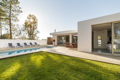 Modern house garden swimming pool and wooden deck. Modern house with garden swimming pool and wooden deck royalty free stock photography